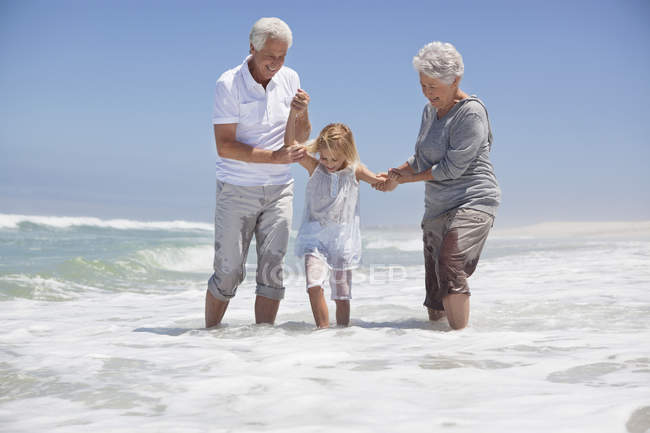 Girl having fun on sea beach with grandparents — Stock Photo