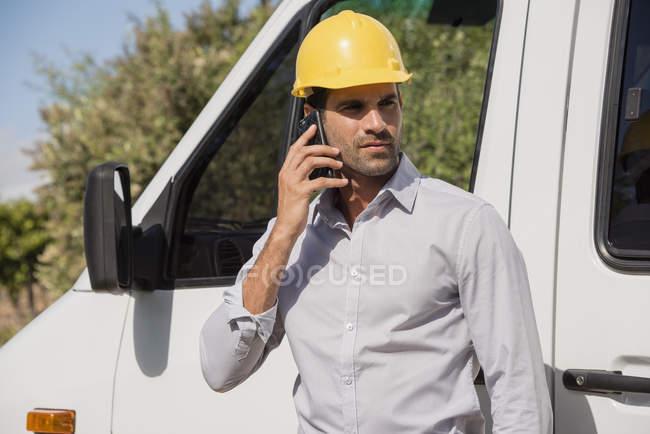 Мужчина-инженер говорит по мобильному телефону перед фургоном — стоковое фото