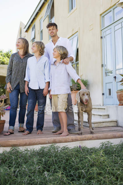 Retrato de família feliz se divertindo no quintal com o cão — Fotografia de Stock