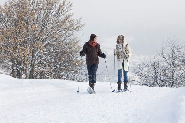 Young couple snowshoeing in winter mountains — Stock Photo