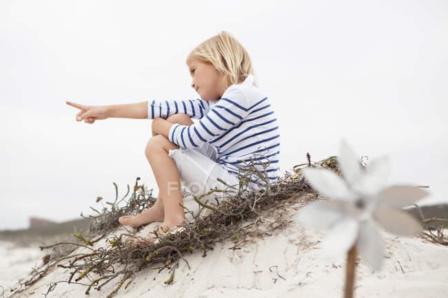 Маленькая блондинка сидя на песке и указывая на расстоянии — стоковое фото