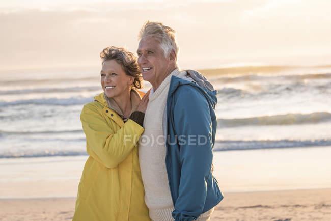 Glückliches Senioren-Paar steht bei Sonnenuntergang am Strand — Stockfoto