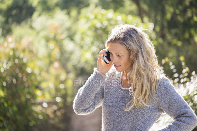 Woman in sweater talking on phone in sunny garden — Stock Photo