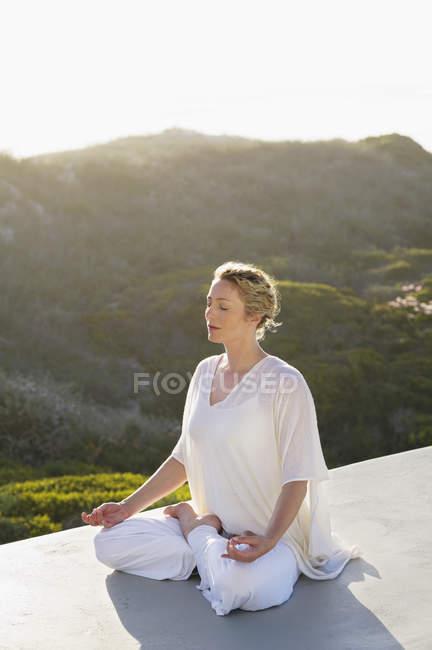 Расслабленная женщина в белом наряде медитирует на природе — стоковое фото
