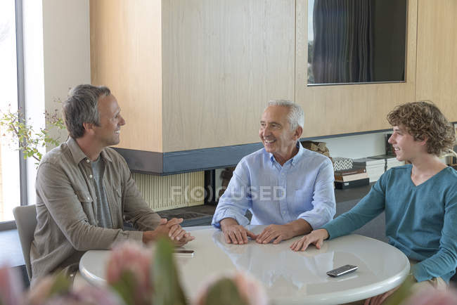 Happy senior man with son and grandson sitting and talking at table in living room — Stock Photo