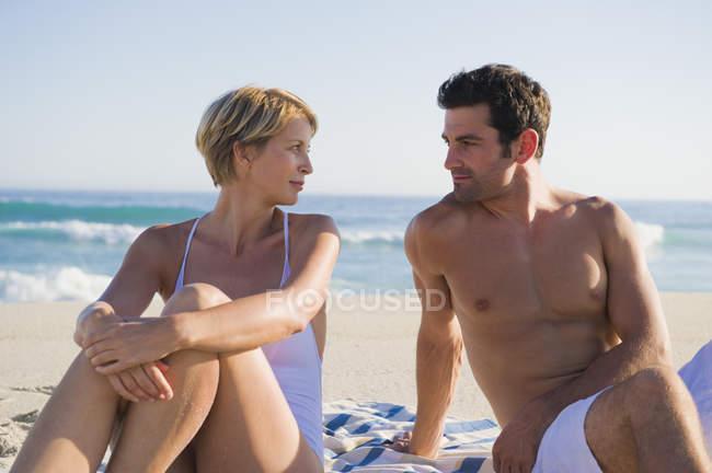 Coppia romantica seduta sulla spiaggia e guardando l'un l'altro — Foto stock