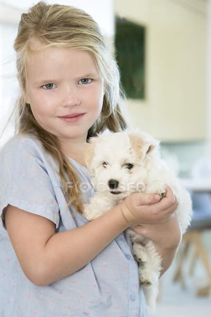 Портрет милой девочки, держащей щенка — стоковое фото