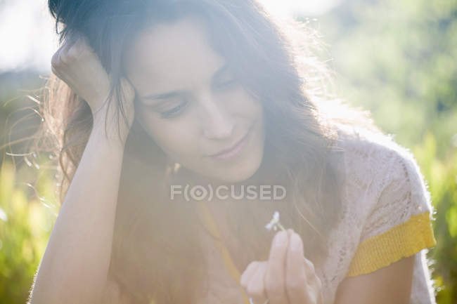 Dreamy woman in sunny nature holding small daisy flower — Stock Photo