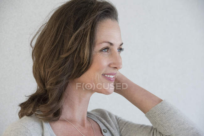 Smiling mature woman standing on grey background — Stock Photo