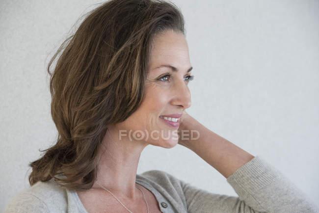 Lächelnde reife Frau steht auf grauem Hintergrund — Stockfoto