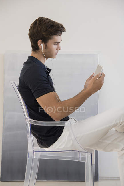 Young man listening music with earphones and smartphone on glass chair at home — Stock Photo