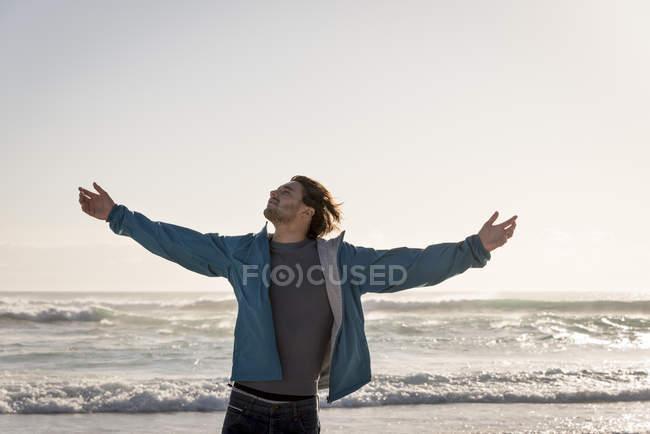 Heureux jeune homme avec les bras tendus debout sur la plage — Photo de stock
