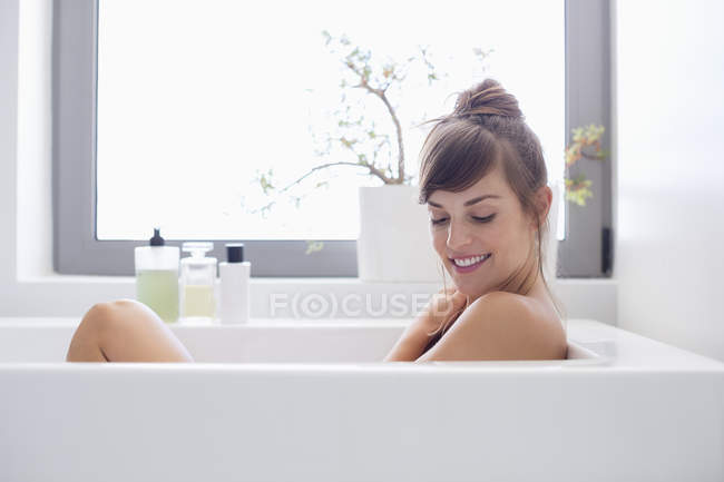 Smiling young woman relaxing in bathtub — Stock Photo
