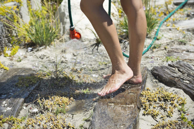Low section of woman washing feet on rock in nature — Stock Photo