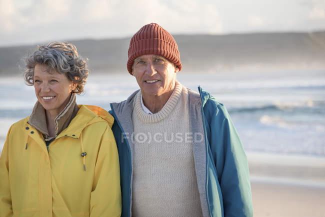 Feliz casal sênior de pé na praia ao pôr do sol — Fotografia de Stock