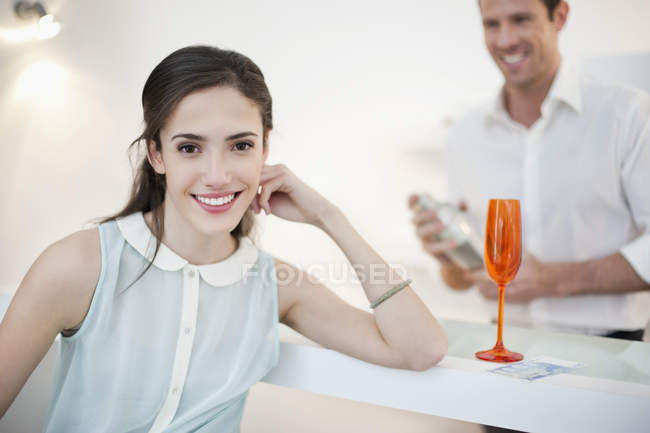 Woman smiling with husband shaking cocktail on background — Stock Photo