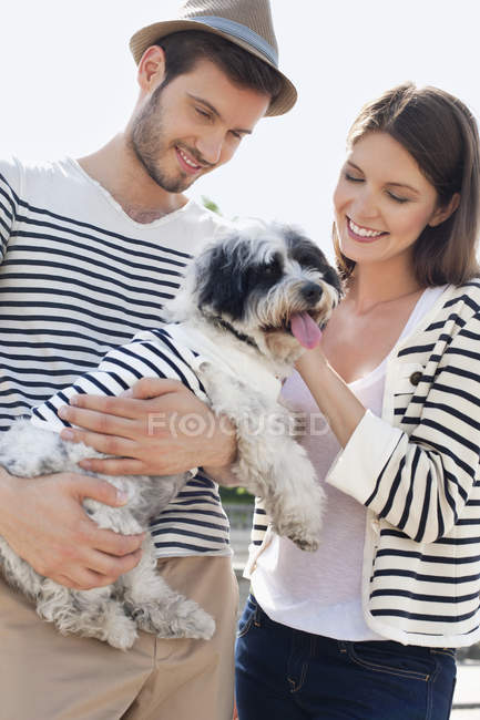 Smiling couple carrying puppy outdoors — Stockfoto