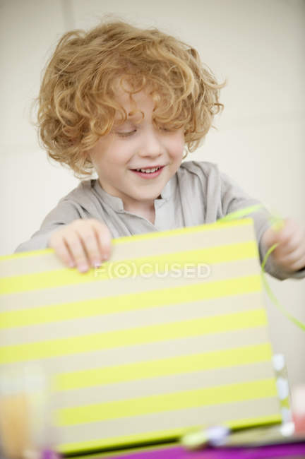 Smiling boy with blonde hair opening birthday present — Stock Photo