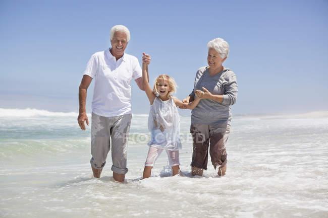 Mädchen vergnügt sich mit Großeltern am Strand — Stockfoto