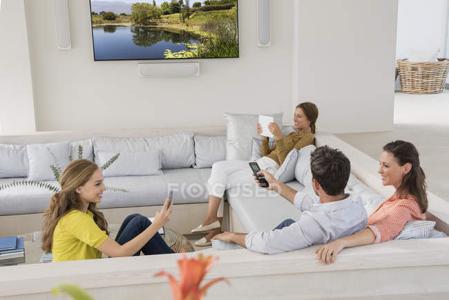 Couple watching television with daughters busy with gadgets — Stock Photo