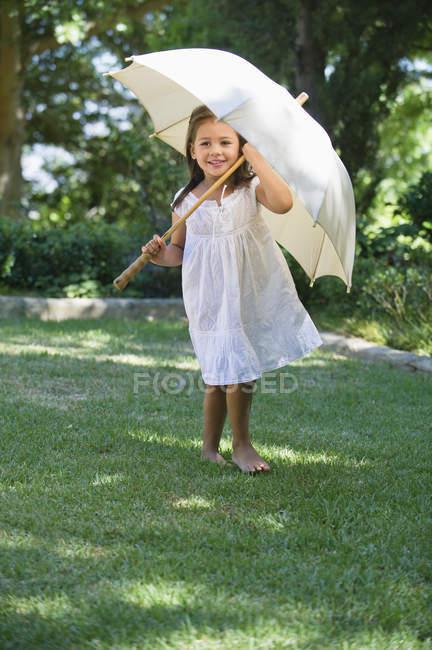 Мила маленька дівчинка в білий літні сукні холдингу парасолька у сонячному саду — стокове фото