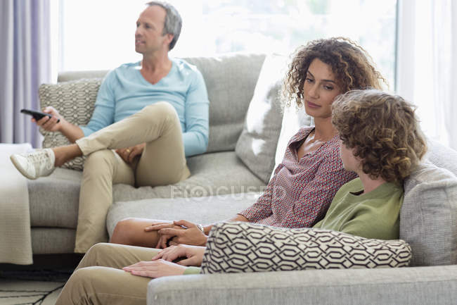 Mother talking to son on sofa while father watching tv on background in living room at home — Stock Photo