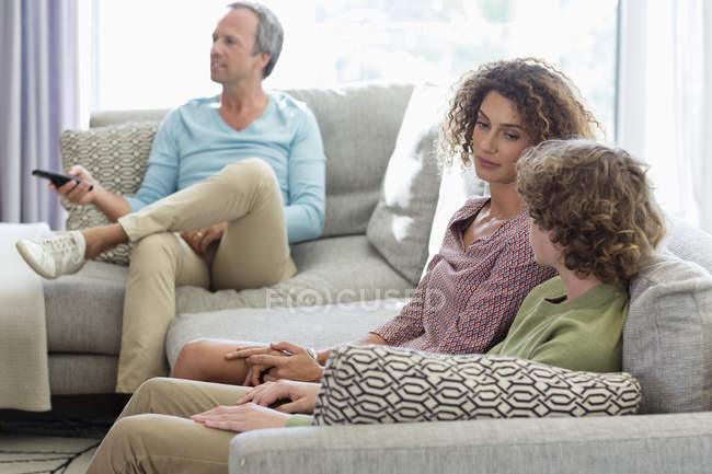 Madre hablando con el hijo en el sofá mientras el padre viendo la televisión en el fondo en la sala de estar en casa - foto de stock