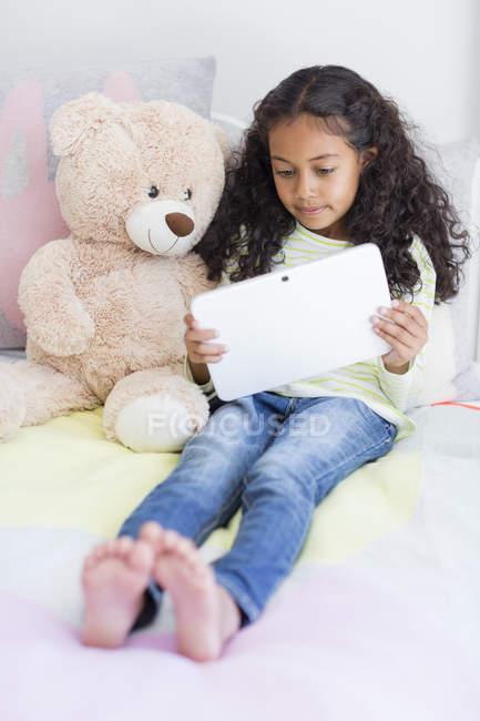 Niña con tableta digital de oso de peluche en la cama - foto de stock