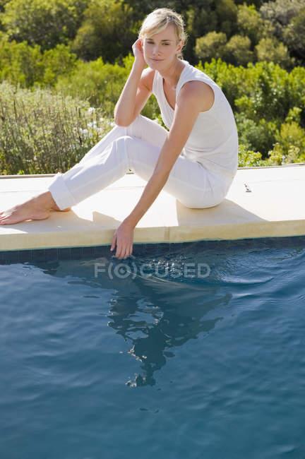 Verträumte entspannte Frau sitzen am Pool und mit Blick auf Wasser — Stockfoto