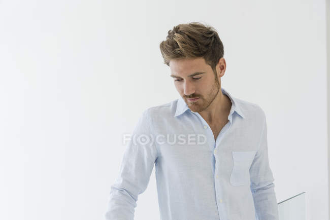 Portrait of elegant young man in white shirt looking down — Stock Photo