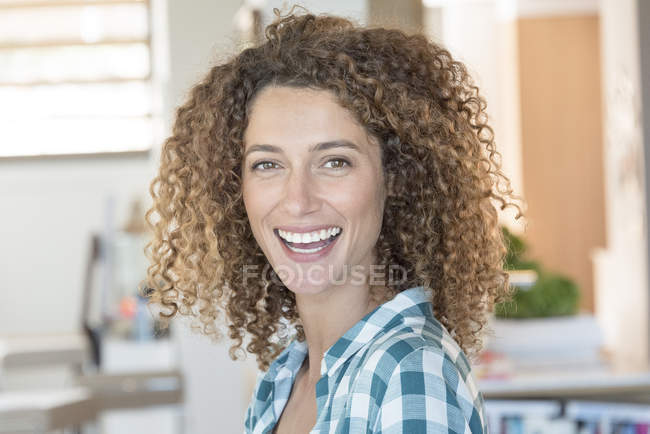 Portrait of smiling woman in checkered shirt — Stock Photo