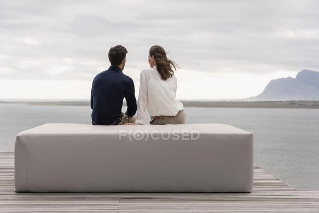 Visão traseira do casal sentado no otomano no lago e olhando para a vista — Fotografia de Stock