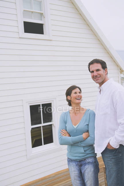 Laughing couple standing together in front of house — Stock Photo