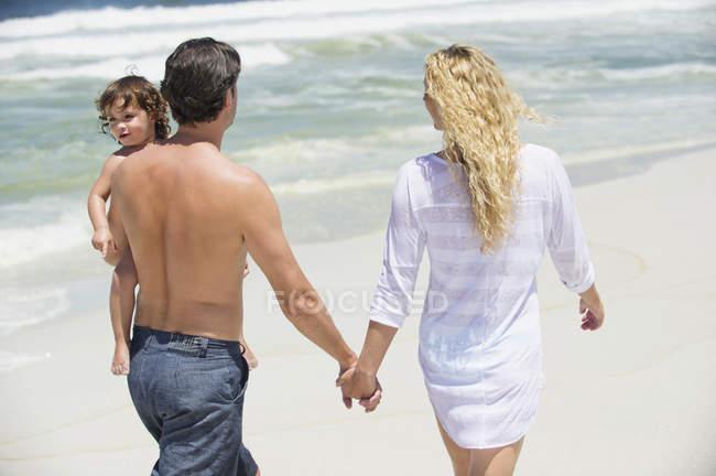 Happy family walking on sea beach — Stock Photo