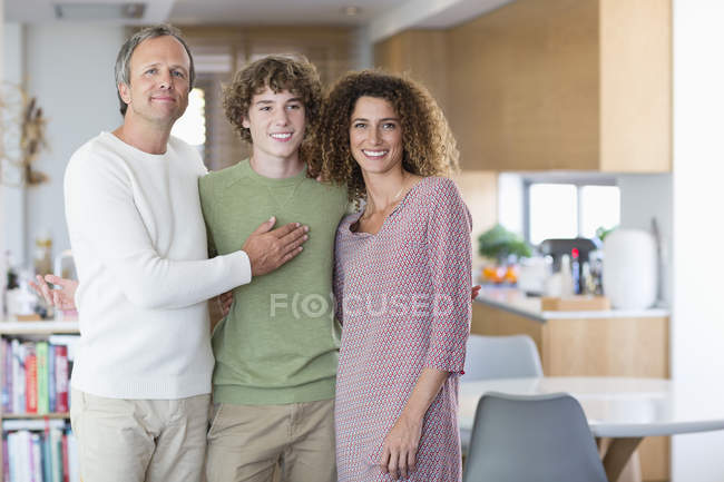 Ritratto della famiglia felice che sorride mentre in piedi a casa insieme — Foto stock