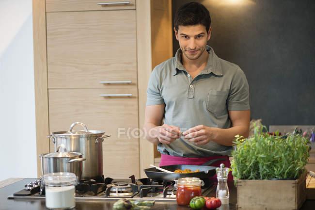 Людина, приготування їжі в кухні і, дивлячись на камеру — стокове фото