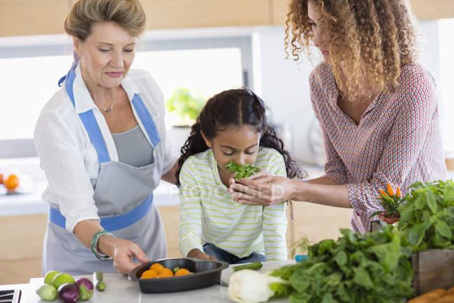 Donna anziana con figlia e nipote che odora di erbe in cucina — Foto stock