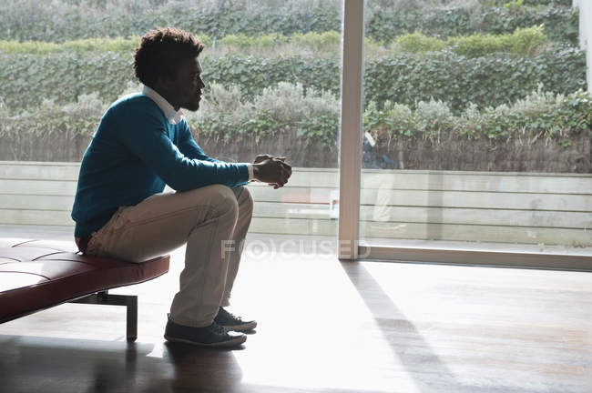 Young man sitting on couch and thinking — Stock Photo