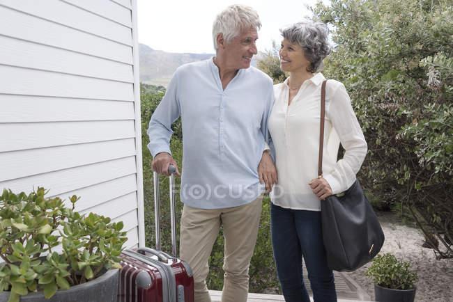 Щаслива пара старший стоячи з чемодан поза домом — стокове фото