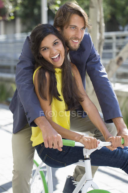 Portrait of couple riding bicycle and smiling on street — Stock Photo