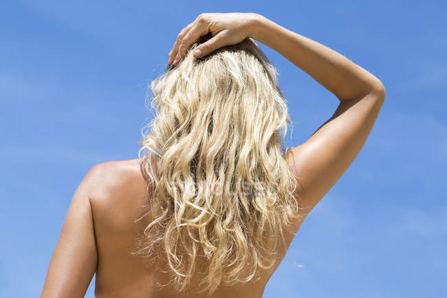 Rear view of shirtless blonde woman with hand in hair against blue sky — Stock Photo