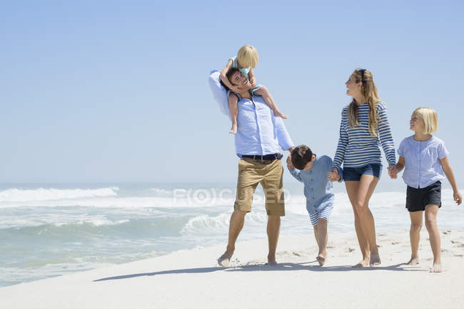 Relaxed family walking on sandy beach — Stock Photo