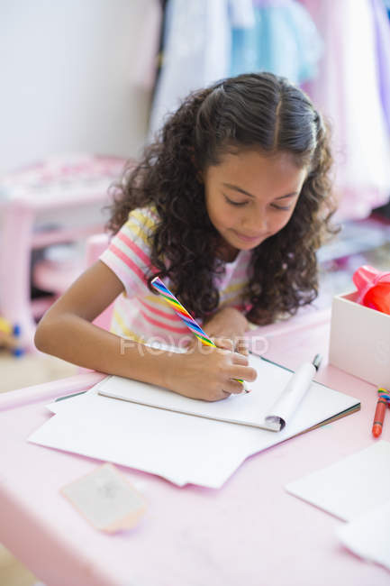 Focused little girl doing homework at pink table — Stock Photo