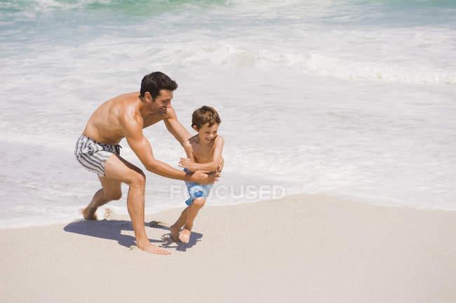 Homem alegre brincando com o filho na praia de areia — Fotografia de Stock