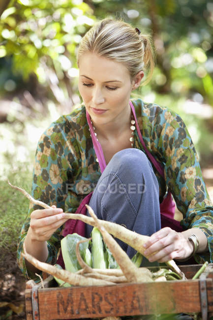 Woman holding fresh picked radishes in garden — Stock Photo