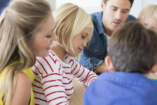 Закри батьки з дітьми, сидячи вдома разом — стокове фото