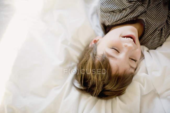 Menino feliz, deitado na cama com os olhos fechados — Fotografia de Stock