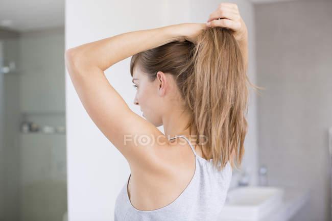 Молода жінка, регулюючи волосся у ванній кімнаті — стокове фото
