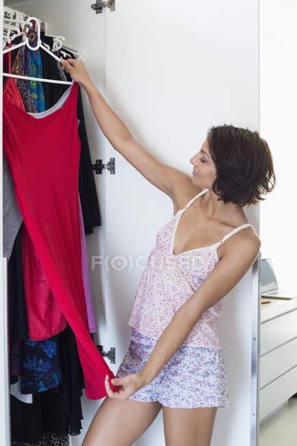 Mulher escolhendo roupas de guarda-roupa em casa — Fotografia de Stock