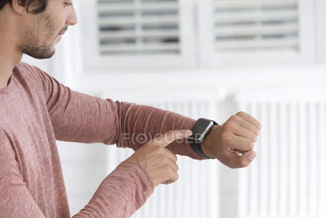Nahaufnahme eines jungen Mannes, der Smartwatch checkt — Stockfoto